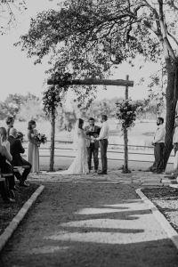 A photo of a wedding ceremony under a grove of trees overlooking a lake
